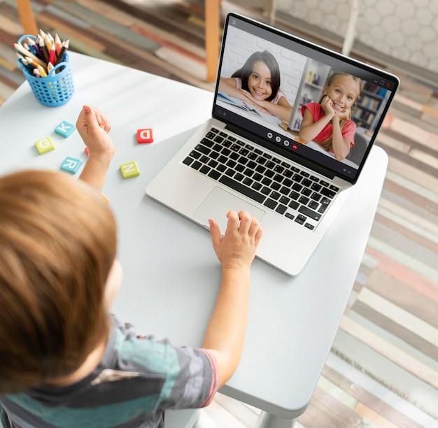 Маленькая девочка разговаривает со своими друзьями на ноутбуке во время видеозвонка