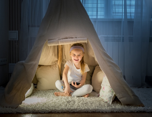 Little girl in teepee tent in room