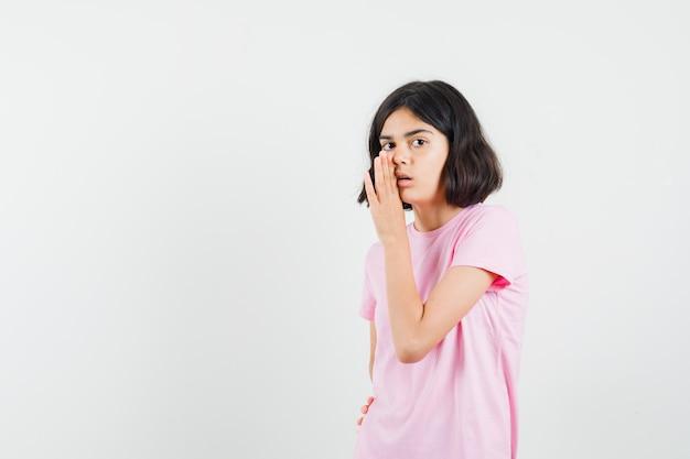 ピンクのtシャツ、正面図で手の後ろに秘密を語る少女。