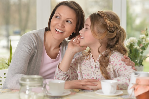 Little girl telling a secret to smiling mother while drinking tea