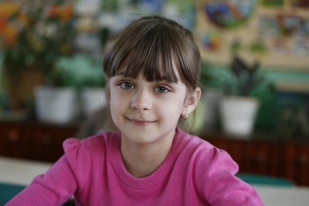 小さな女の子、子供はテーブルで幼稚園に座って、笑っています。