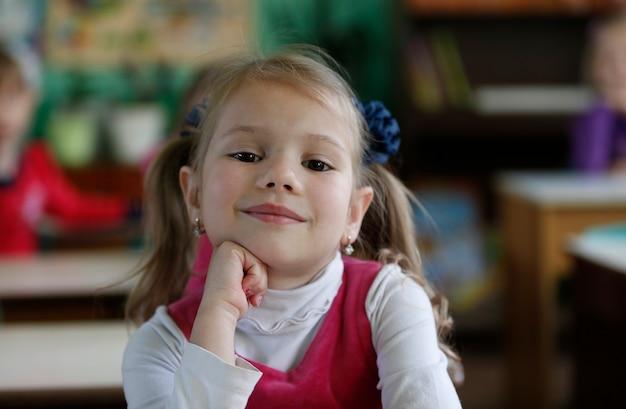 Маленькая девочка, ребенок сидит в детском саду за столом, улыбается.