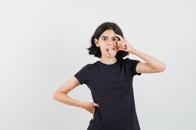 Маленькая девочка думает, высунув язык в черной футболке и выглядит смешно, вид спереди.