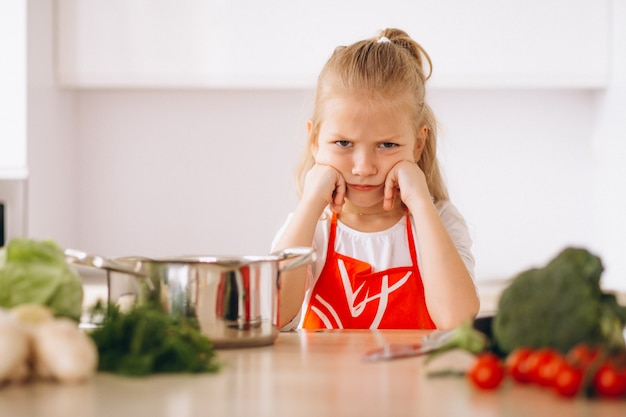 Little girl thinking what to cook at the kitchen