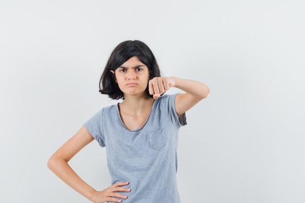 Bambina che minaccia con il pugno in maglietta e sembra dispettosa. vista frontale.