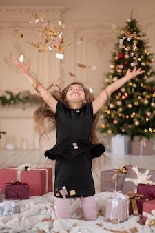 小さな女の子が紙吹雪を投げます。クリスマスの魔法。幸せな子供時代の楽しい瞬間。