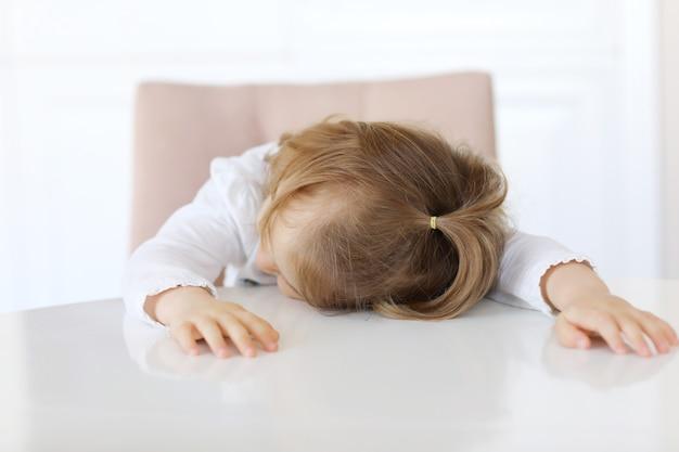 Маленькая девочка устала ждать завтрака и заснула белый стол