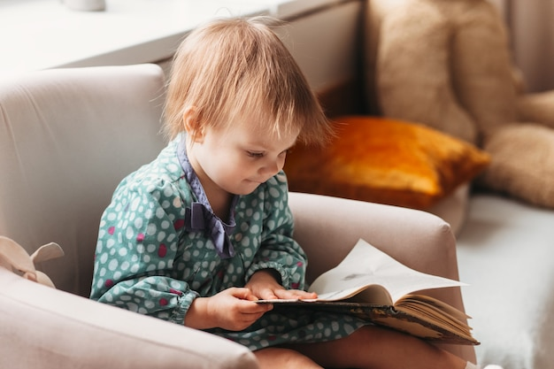 Little girl todler sits in a chair and reads a book. development, education, childhood