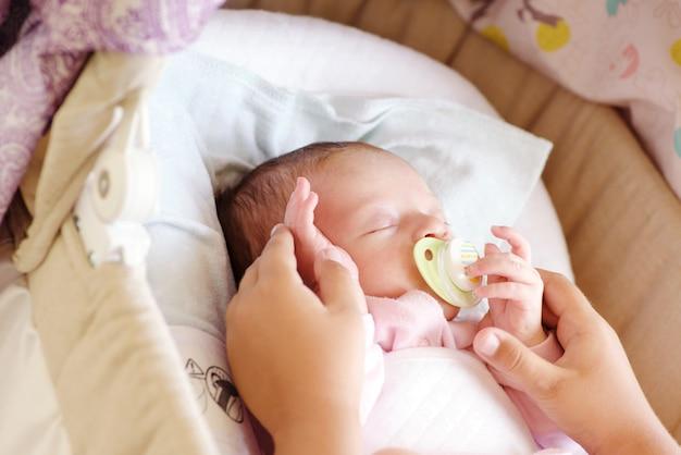 ベビーベッドで生まれたばかりの赤ちゃんの手に触れる少女