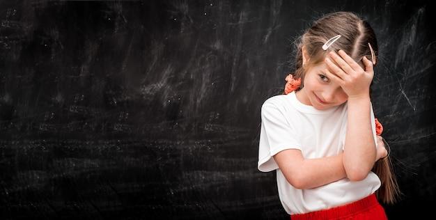 黒板の前で額に触れる少女