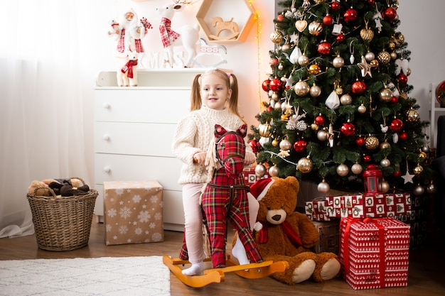 Little girl on toy horse at home near christmas tree and gift boxes