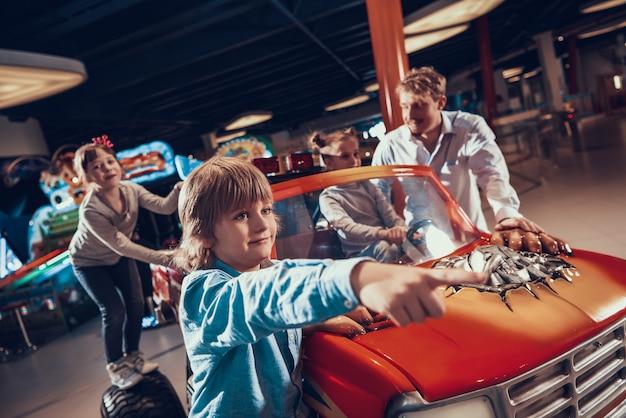Little girl on toy monster car in amusement center