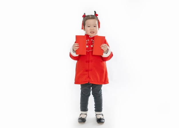 A little girl in traditional chinese dress holds a new year's red envelope in her hand