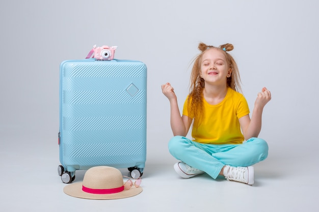 A little girl traveler sits next to a suitcase and meditates on white