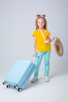 Little girl traveler with a suitcase on a white background