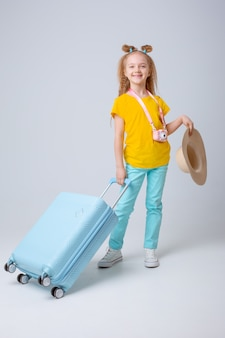 Little girl traveler with a suitcase on white