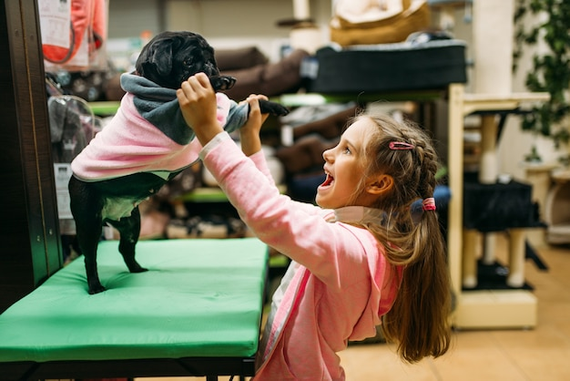 Little girl try on clothes for puppy in pet shop. kid customer buying dogs overall in petshop, goods for domestic animals
