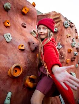 Маленькая девочка пробует стену для скалолазания
