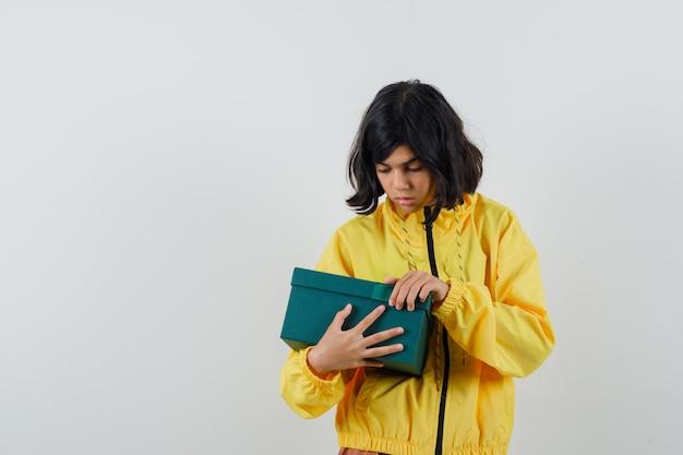 Маленькая девочка пытается открыть подарочную коробку в желтой толстовке с капюшоном и смотрит с любопытством. передний план.