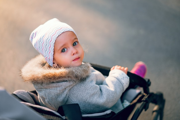 The little girl turns back sitting in a baby carriage on a walk in the park.