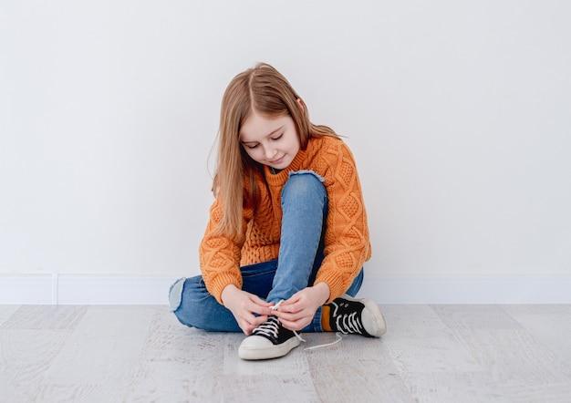 壁の近くの床に座っている間、ガムシューにレースを結ぶ少女