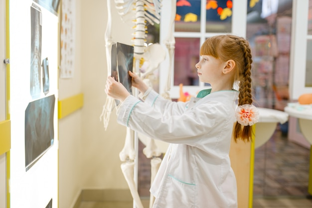 Little girl in uniform looks at the x-ray,