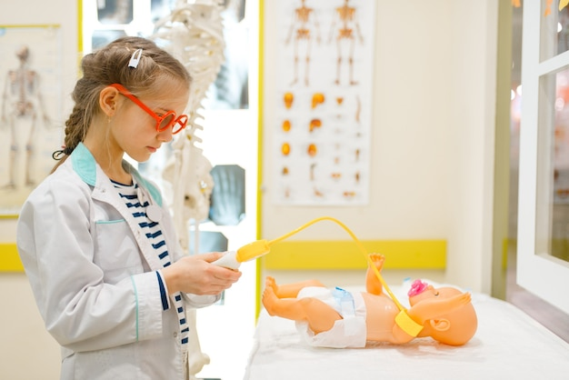 Little girl in uniform playing doctor with doll