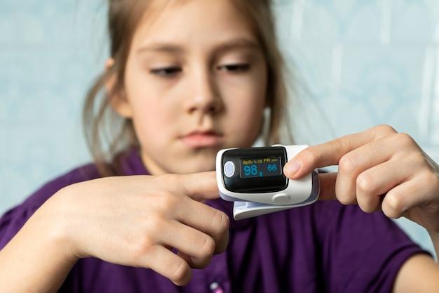 맥박과 산소 수준을 측정하는 데 사용되는 어린 소녀. 모니터링을 위해 손가락에 맥박 산소 농도계를 착용한 환자