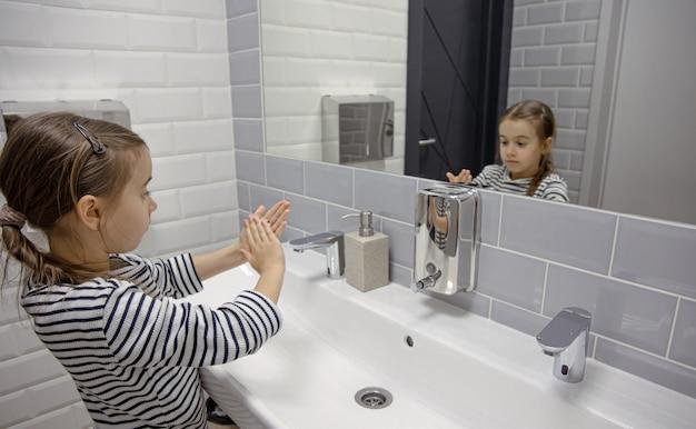 어린 소녀는 액체 비누를 사용하여 손을 씻습니다.