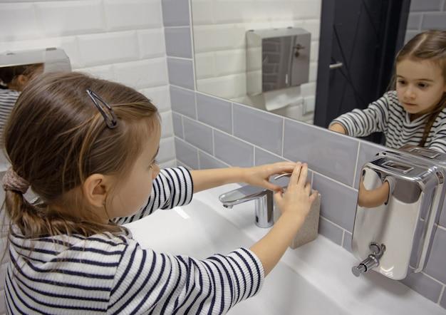 La bambina usa il sapone liquido per lavarsi le mani.