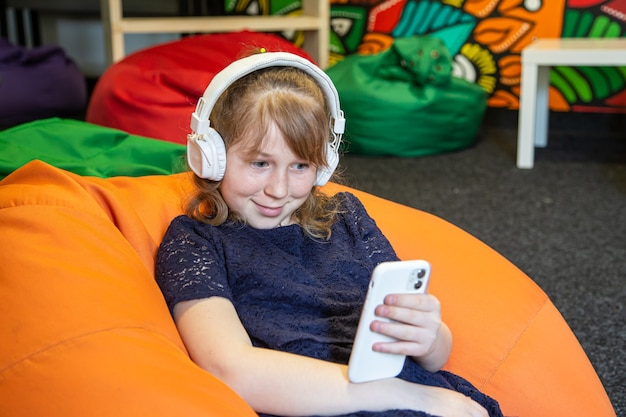Little girl uses phone and listens to music with headphones while sitting on bag chair.