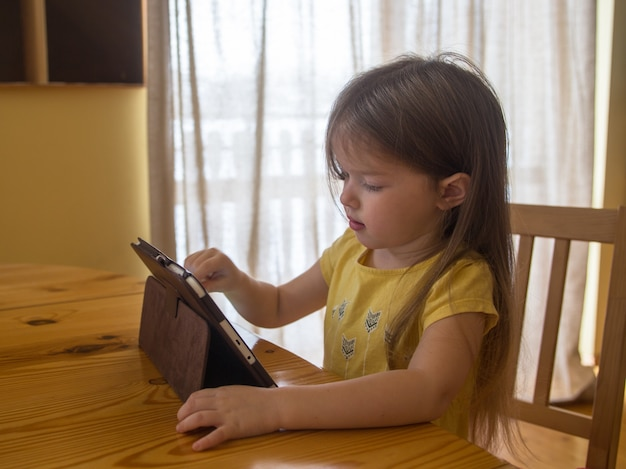 Little girl uses tablet, watches cartoons, plays games