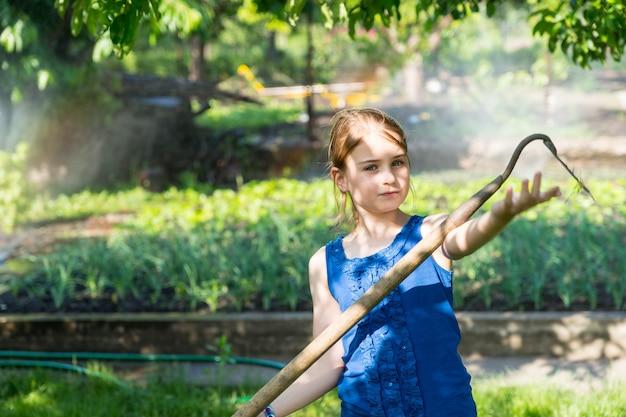 鍬を使って庭に手を伸ばし、春野菜を後ろに向けて真剣な表情で刃に触れる少女