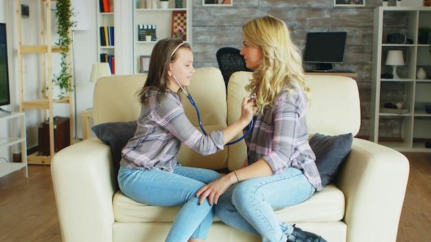聴診器を使用して、リビングルームのソファに座っている母親の心を聞く少女。医者をしている女の子。