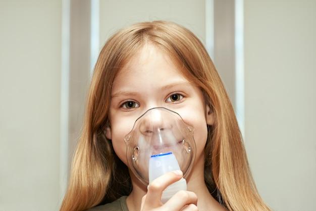 室内で吸入器を使用して小さな女の子