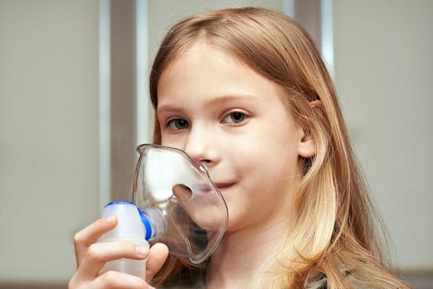 屋内で吸入器を使用している少女