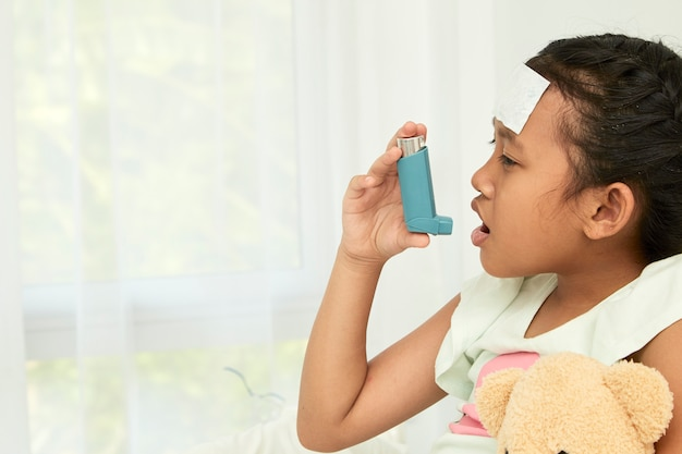 Little girl using asthma inhaler