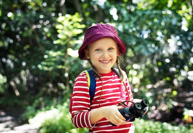 Little girl using binoculars in the forest