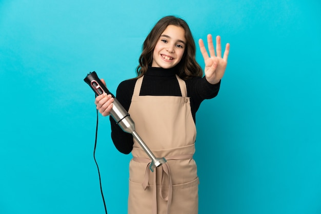 Little girl using hand blender isolated on blue background happy and counting four with fingers