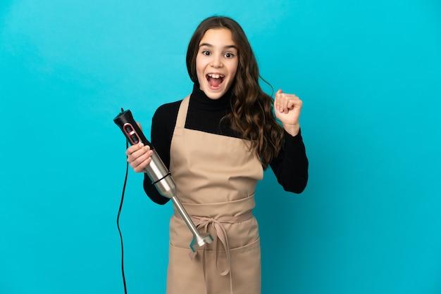 승자 위치에서 승리를 축하하는 파란색 배경에 고립 핸드 블렌더를 사용하는 어린 소녀
