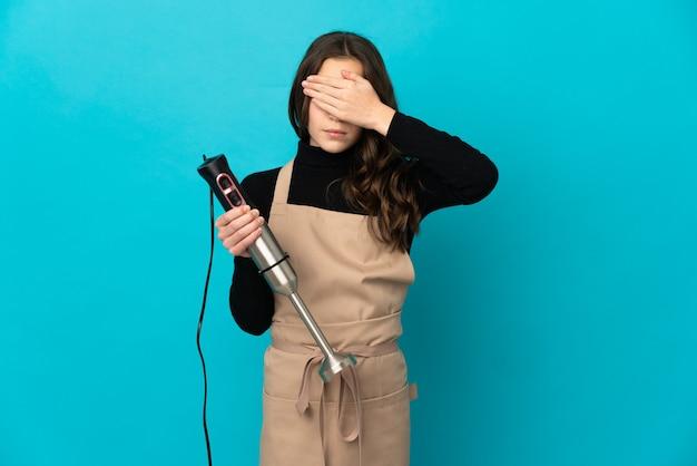 Маленькая девочка, используя ручной блендер, изолированные на синем фоне, закрывая глаза руками. не хочу что-то видеть