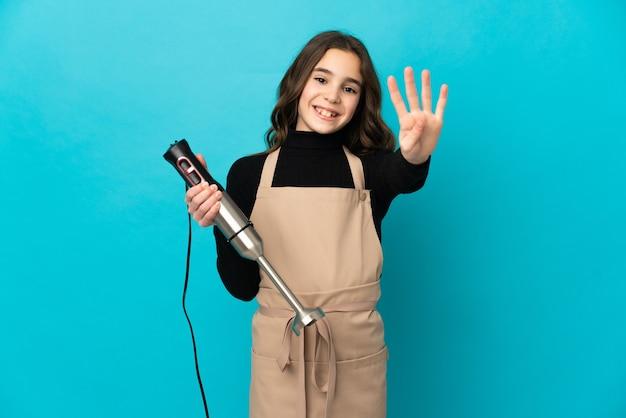 Маленькая девочка с помощью ручного блендера, изолированного на синем фоне, счастлива и считает четыре пальцами
