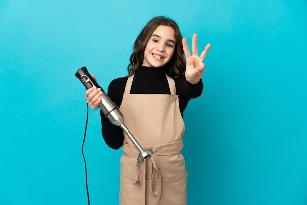 Маленькая девочка с помощью ручного блендера, изолированного на синем фоне, счастлива и считает три пальцами