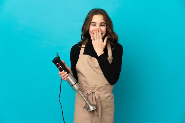 Маленькая девочка, используя ручной блендер, изолированные на синем фоне, счастливая и улыбающаяся, прикрывая рот рукой