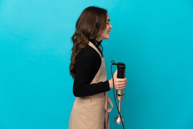 핸드 블렌더를 사용하는 어린 소녀는 측면 위치에서 웃고 파란색 배경에 고립
