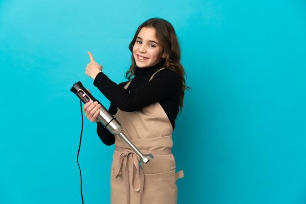 Маленькая девочка, используя ручной блендер, изолированные на синем фоне, указывая назад