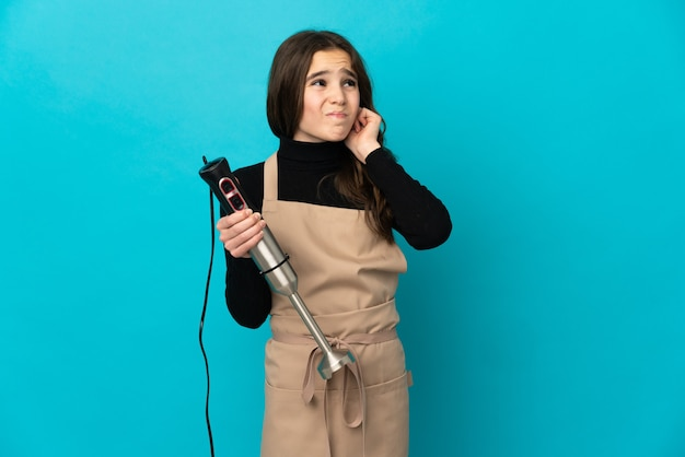 欲求不満と耳を覆っている青い壁に分離されたハンドブレンダーを使用して少女