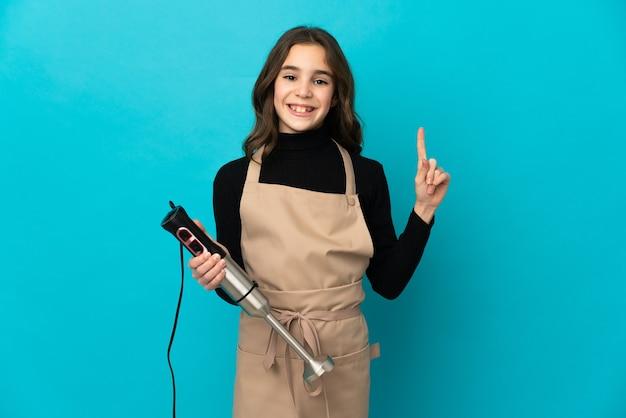 파란색 벽 표시에 고립 된 핸드 블렌더를 사용하는 어린 소녀와 최고의 기호에 손가락을 들어 올려