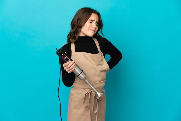 노력을 한 데 대한 요통으로 고통받는 파란색 벽에 고립 된 핸드 블렌더를 사용하는 어린 소녀
