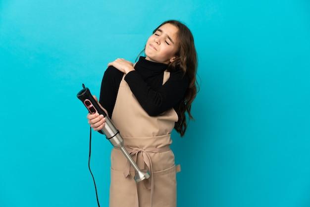 Маленькая девочка, использующая ручной блендер, изолирована на синей стене, страдает от боли в плече из-за того, что приложила усилие